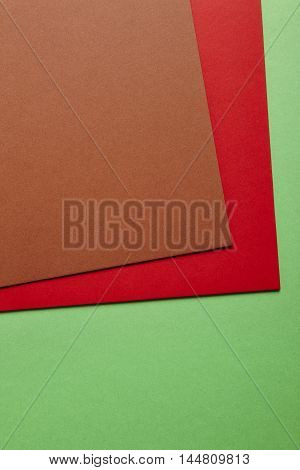 Colored cardboards background in brown red green tone. Copy space. Vertical