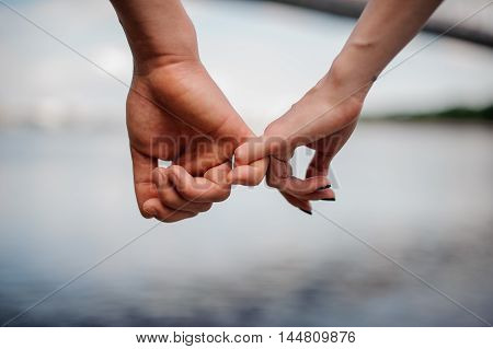 Happy couple holding hands together. water background