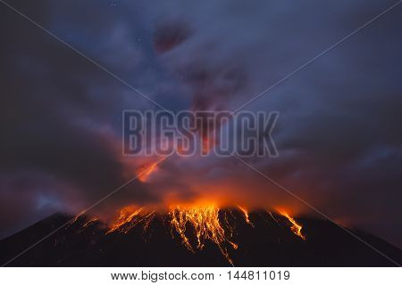 QUITO ECUADOR - March 4 2016: Tungurahua Volcano is one of the most active of Ecuador you can see an explosion at 4 am with the moon shining through the clouds.
