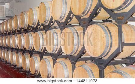 Steel shelving with rows of new oak barrels with wine on a warehouse in winery