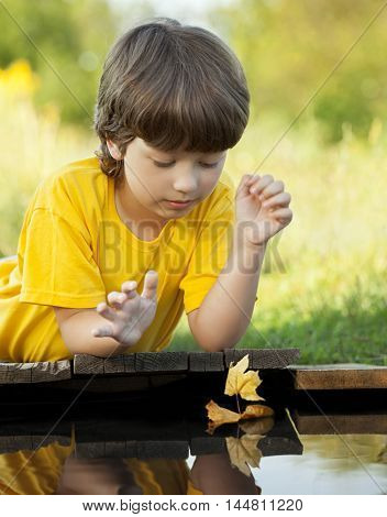 boy play with autumn leaf ship in water, chidren in park play with boat in river