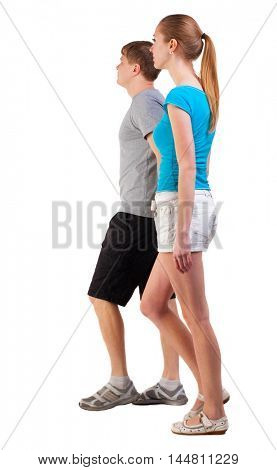 Back view of going young couple (man and woman). walking beautiful friendly girl and guy in shorts together. Rear view people collection.  newlyweds go on a journey. backside view of person