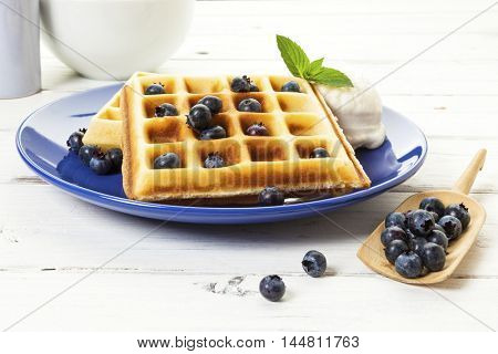 Belgian waffles with blueberries and vanilla ice cream on blue plate, spare fruit on wooden shovel, rustic table