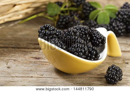 Blackberries on yellow serving spoon, rustic background