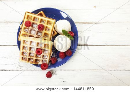 Belgian waffles with raspberries, icing sugar and vanilla ice cream on blue plate, high angle view, copy space