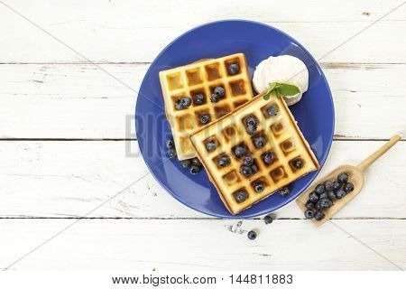 Belgian waffles with blueberries and scoop of vanilla ice cream on blue plate, high angle view with copy space