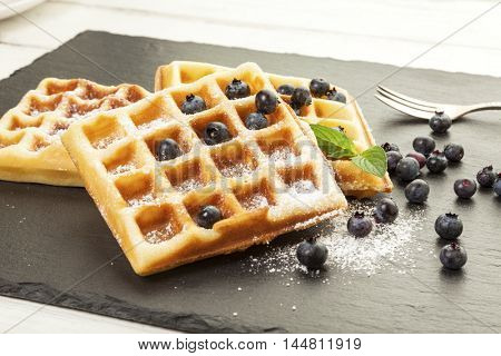 Handmade belgian waffles with blueberries and powdered sugar served on black slate