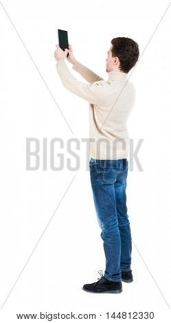Back view of man with tablet. Standing young guy. Rear view people collection.  backside view of person.  Isolated over white background. Curly boy in a white warm sweater tablet takes something in