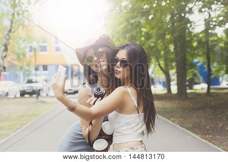 Two girls friends outdoors taking selfie photos at digital camera. Young female tourists in boho chic fashion clothes, laughing and having fun in summer park. Travelling together, lifestyle portrait.