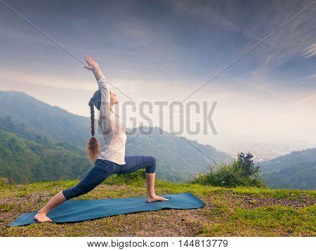 Yoga outdoors - sporty fit woman doing Ashtanga Vinyasa Yoga asana Virabhadrasana 1 Warrior pose posture in HImalayas mountains on sunset