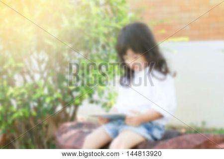 de-focused Happy preschooler Asian child playing with tablet pc sitting in garden