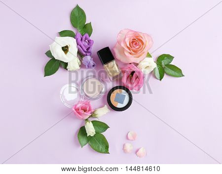 Eye shadows and flowers on purple background