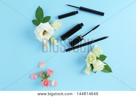 Mascara and flowers on blue background