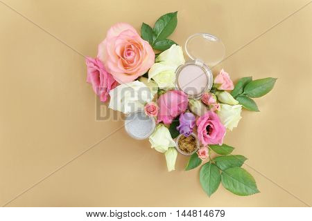 Eye shadows and flowers on beige background