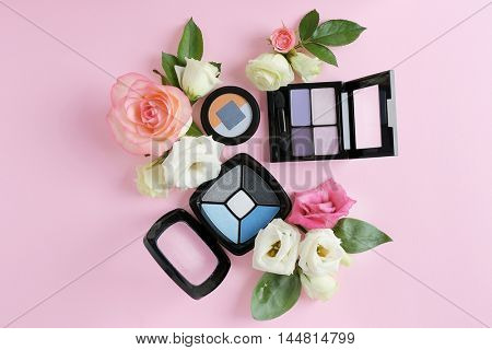 Eye shadows and flowers on pink background