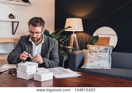 Focused young entrepreneur sitting at a table at home heating up a stamp while preparing packages for delivery to customers