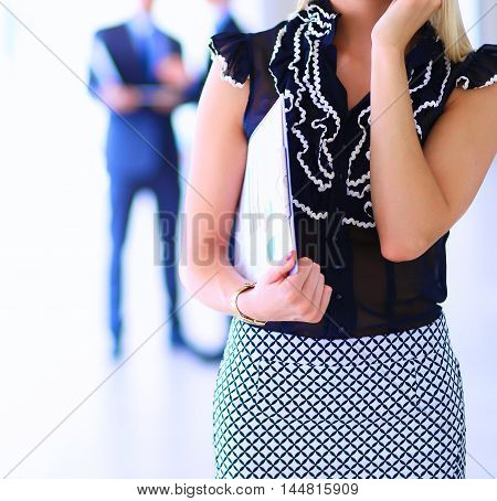 Beautiful businesswoman using cell phone , standing in office .