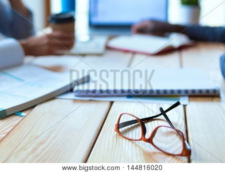 Attractive woman sitting at desk in office, working with laptop , having takeaway coffee.