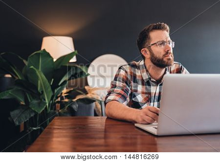 Young entrepreneur looking thoughtful while sitting at a table at home using a laptop