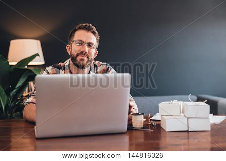 Portrait of a smiling young entrepreneur sitting at table at home using a laptop next to boxes ready for delivery to customers