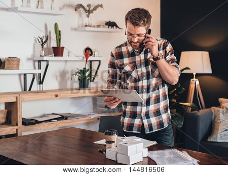 Young entrepreneur standing in his living room talking on a cellphone and using a digital tablet, in front of a table with boxes ready for delivery to customers