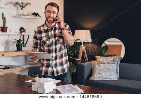Portrait of a young entrepreneur standing in his living room, talking on a cellphone and using a digital tablet, in front of a table with boxes ready for delivery to customers