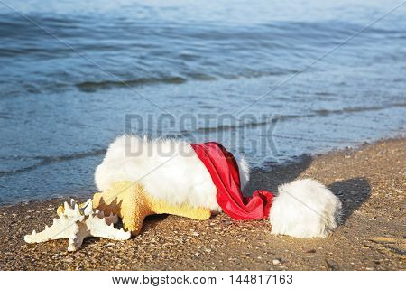 Santa hat with sea stars on beach. Christmas holiday concept
