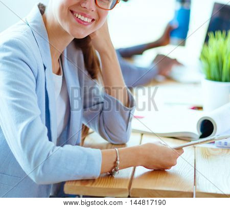 Business woman sitting in her office using a tablet computer