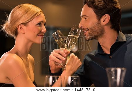 Young happy couple toasting with glass of champagne on romantic date at luxury restaurant. Portrait of loving couple celebrating drinking champagne. Young couple enjoying valentines day or new year.