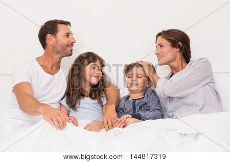 Happy family with two children under the blanket. Man and woman in a conversation while playing with children. Daughter and son looking at each other while parents talking.