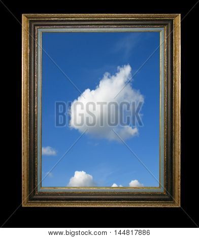 Old vintage wooden frame on a black background with the image of blue sunny sky and fluffy clouds in it.