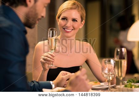 Happy young couple celebrating birthday. Beautiful woman raising a toast. Young couple in a restaurant for a date. Smiling woman at luxury restaurant with her boyfriend celebrate their anniversary.