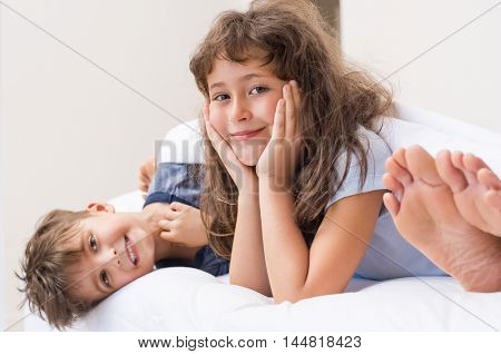 Happy children in pajamas lying on bed and looking at camera. Feet of mother sleeping while son and daughter lying looking at camera. Young children not sleepy lying on bed in parents bed room.