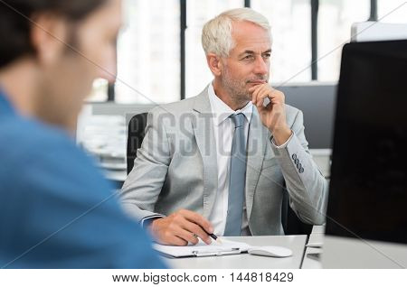 Senior businessman checking accounts in computer while tallying from report. Manager in formal reading report on desktop computer. Close up of a senior employee working with a junior employee.