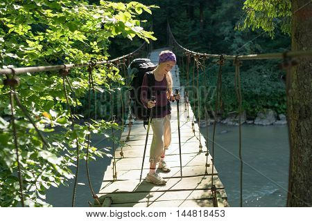 Smiling brave girl with a backpack goes on the suspension bridge in the rays of the rising sun . Travel in the Carpathian Mountains.
