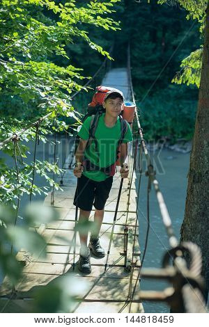 Asian teenager with a backpack standing on the suspension bridge over mountain river. Ukrainian Carpathians
