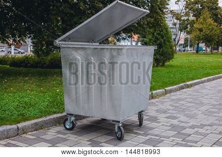 New galvanized garbage container on wheels and with the lid open standing on the road near the curb in the park.
