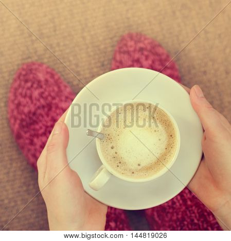 frothy coffee with milk in the hands of the person clothed in warm socks top view / coffee in a warm home environment