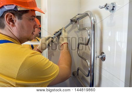 Male plumber repairing the battery in a helmet and with wrench