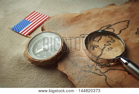 Old map with compass, American flag and magnifier on sand. Happy Columbus day concept