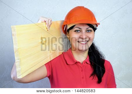Girl the builder in a helmet with a plank of wood. Close portrait of a smile