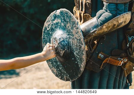 Little boy rests his fist on the knight bruised cracked worn shield