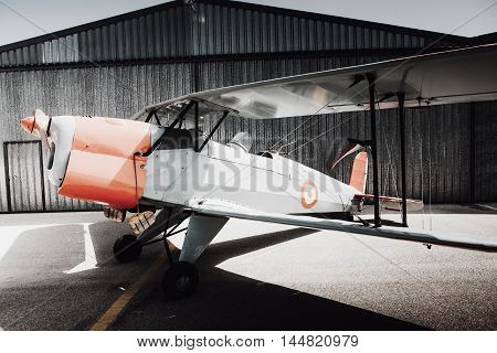 Old vintage plane parked at the aerodrome, view from side.