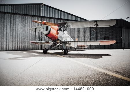 Old vintage plane parked in front of the hangar.