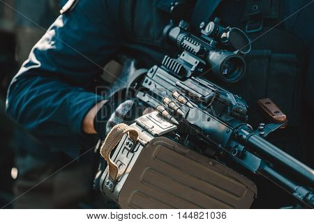 A soldier on a mission runs carrying a gun with a telescopic sight.