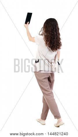 back view of standing young beautiful woman using a mobile phone. Long-haired curly girl holding a tablet in front of him.