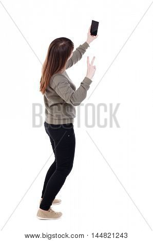 back view of standing young beautiful woman using a mobile phone. girl watching. Girl showing victory sign making selfie.