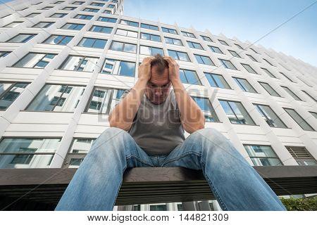 Sad middle age man portrait outdoors. bottom view