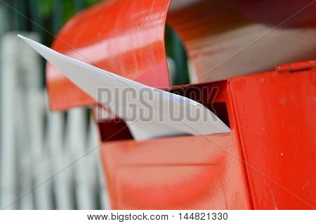 letter in red mail box on home fence