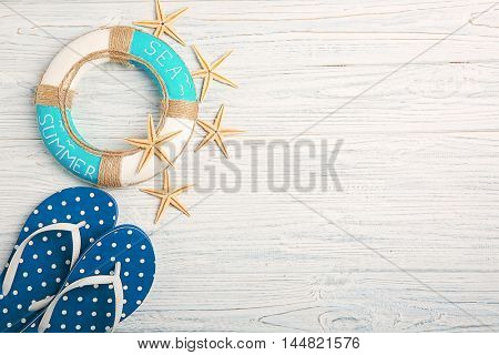 Flip flops with lifebuoy on wooden background